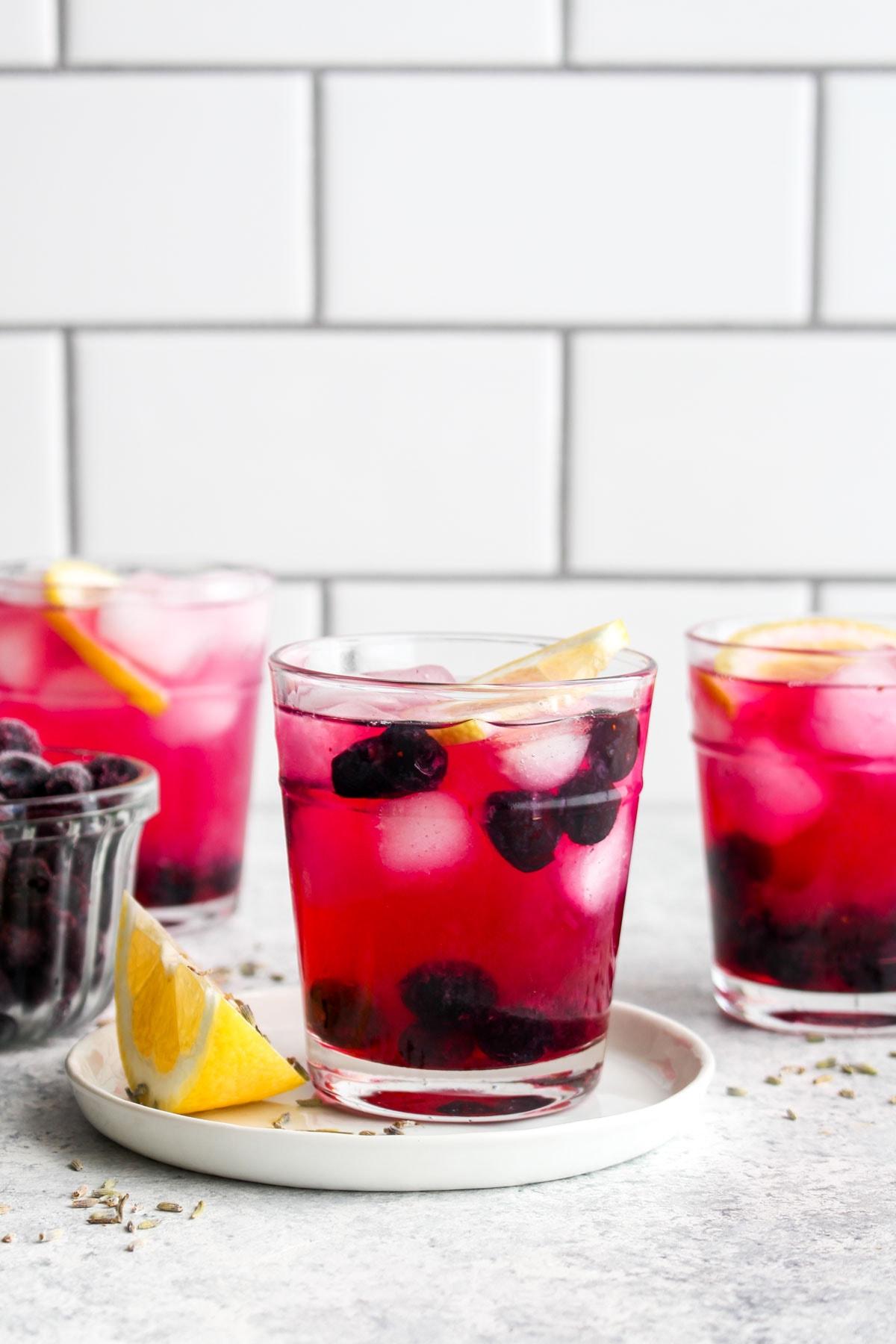 Three glasses of blueberry lavender lemonade.