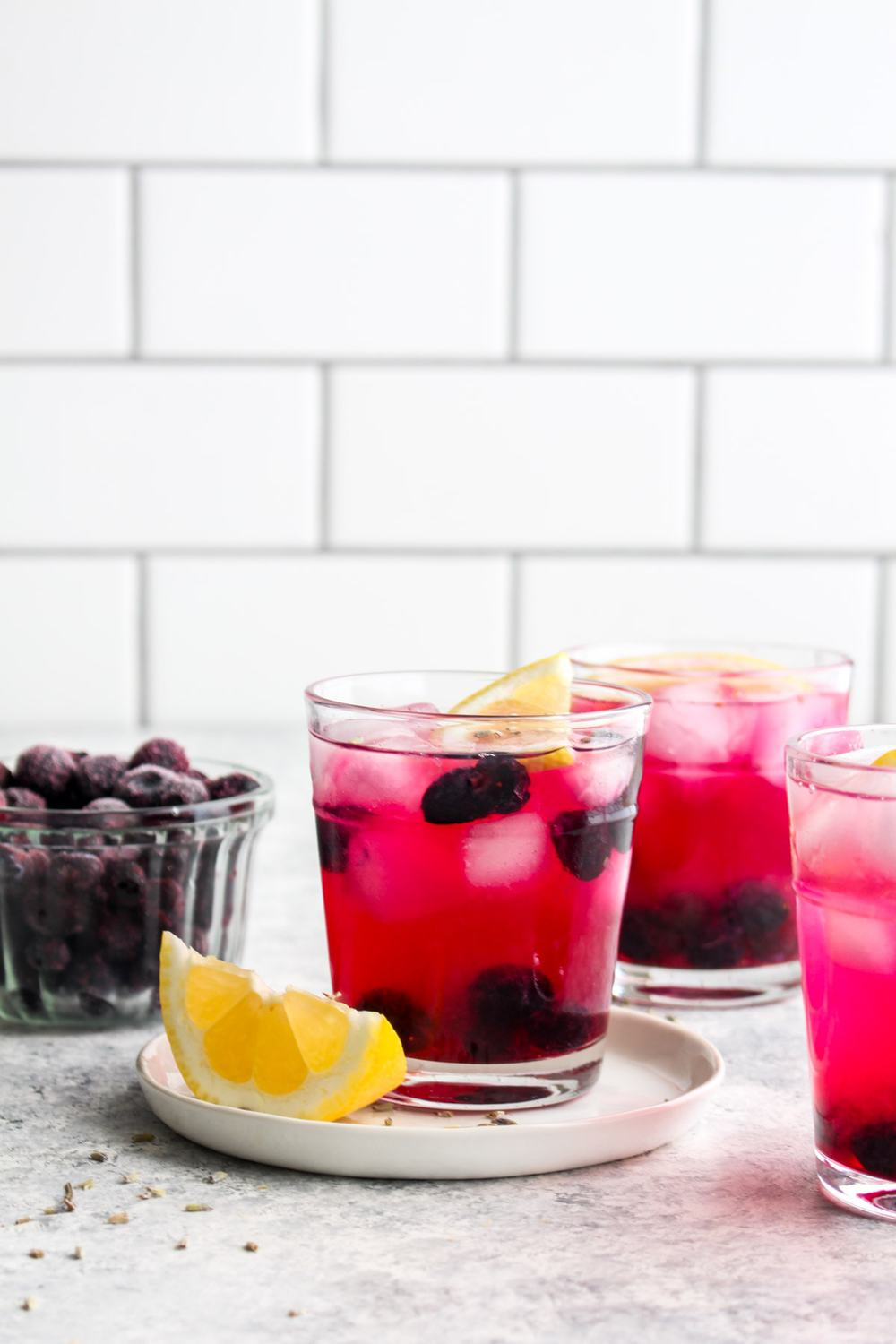 Three glasses of blueberry lavender lemonade on ice with blueberries and lemon.