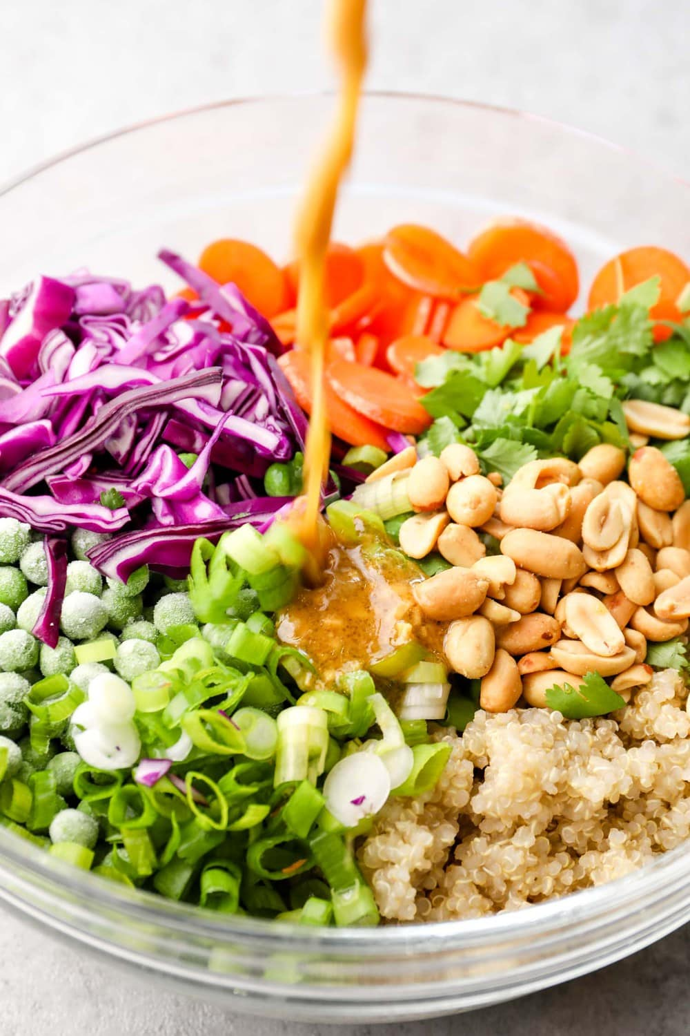 Dressing being poured into Asian Quinoa Salad.