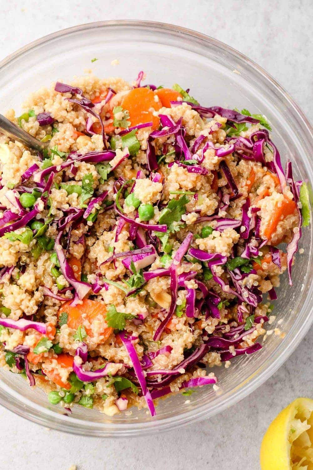 Asian Quinoa Salad tossed with the ginger dressing in a mixing bowl.