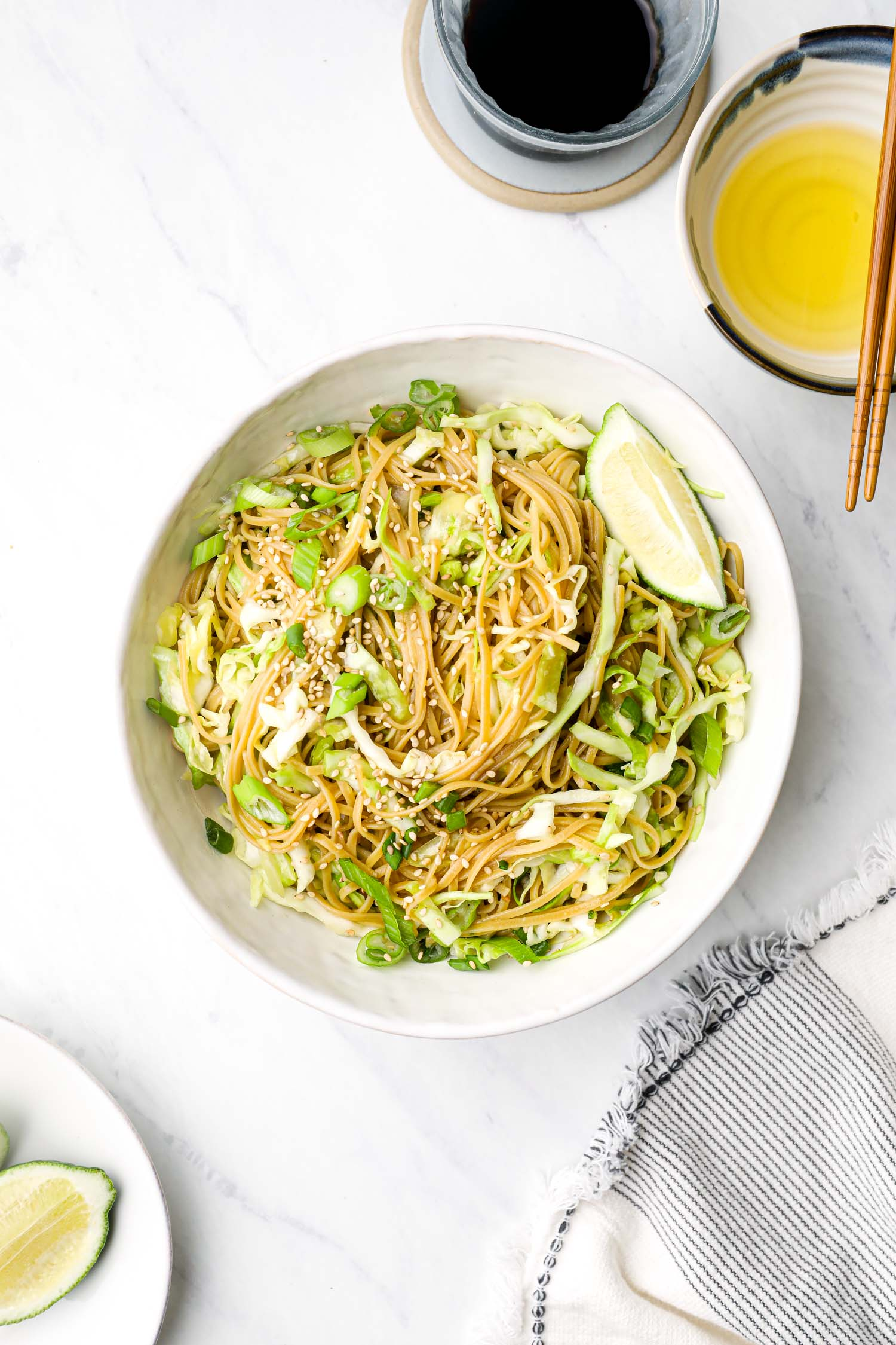 Gluten free Sesame Cabbage Noodles in a white bowl with lime.