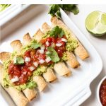 A white baking dish filled with potato taquitos and topped with guacamole and salsa.