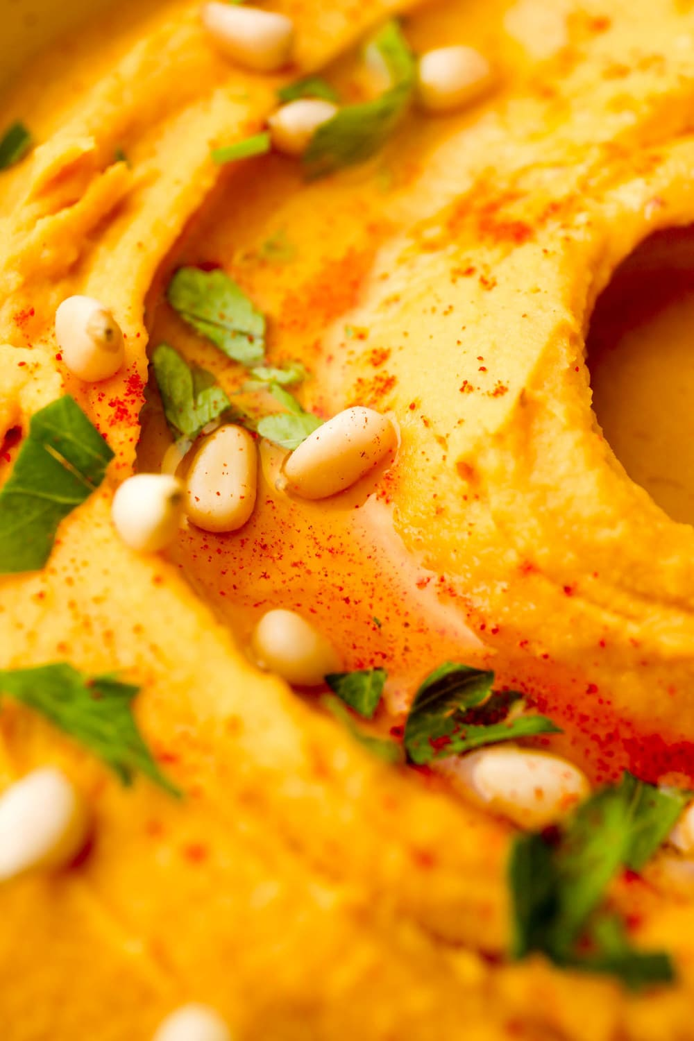 A close up of Sweet Potato Hummus with pine nuts.