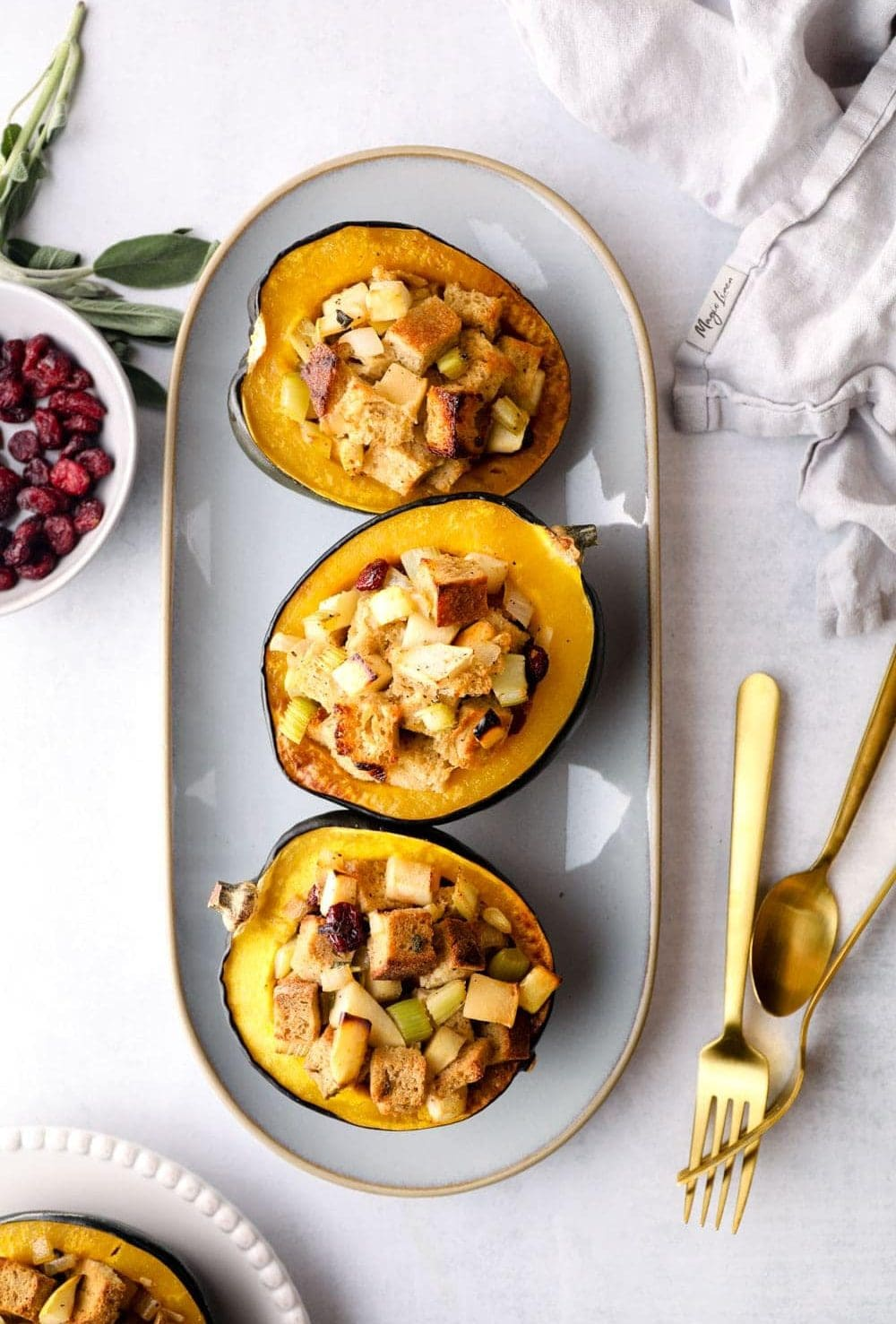 Stuffed Acorn Squash on a platter with cranberries, sage, and gluten free bread