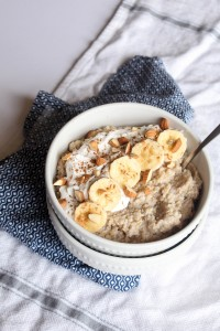 A bowl of Breakfast Quinoa rice Pudding with sliced banana, almonds, and coconut whipped cream.