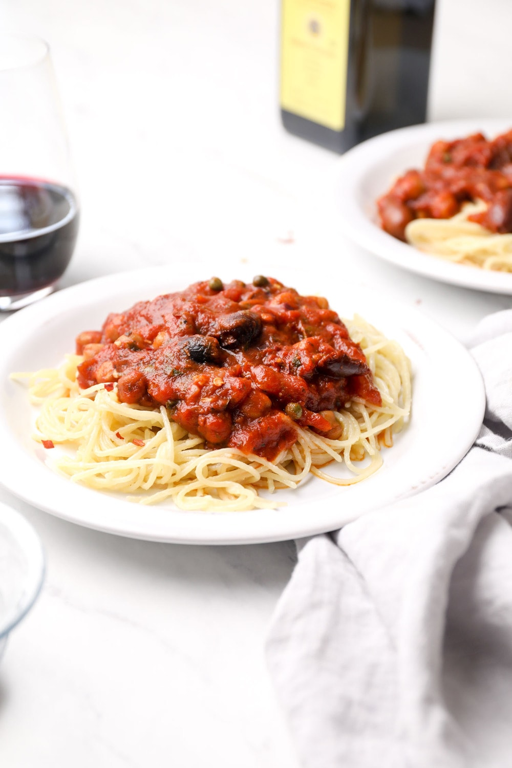 A plate of gluten free pasta with chickpea puttanesca sauce.