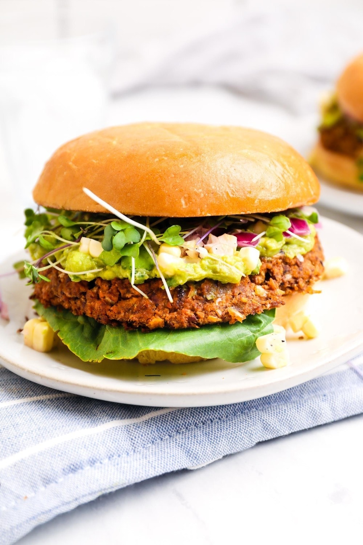 A California Burger with lettuce, guacamole, corn salsa, sprouts and a gluten free bun.