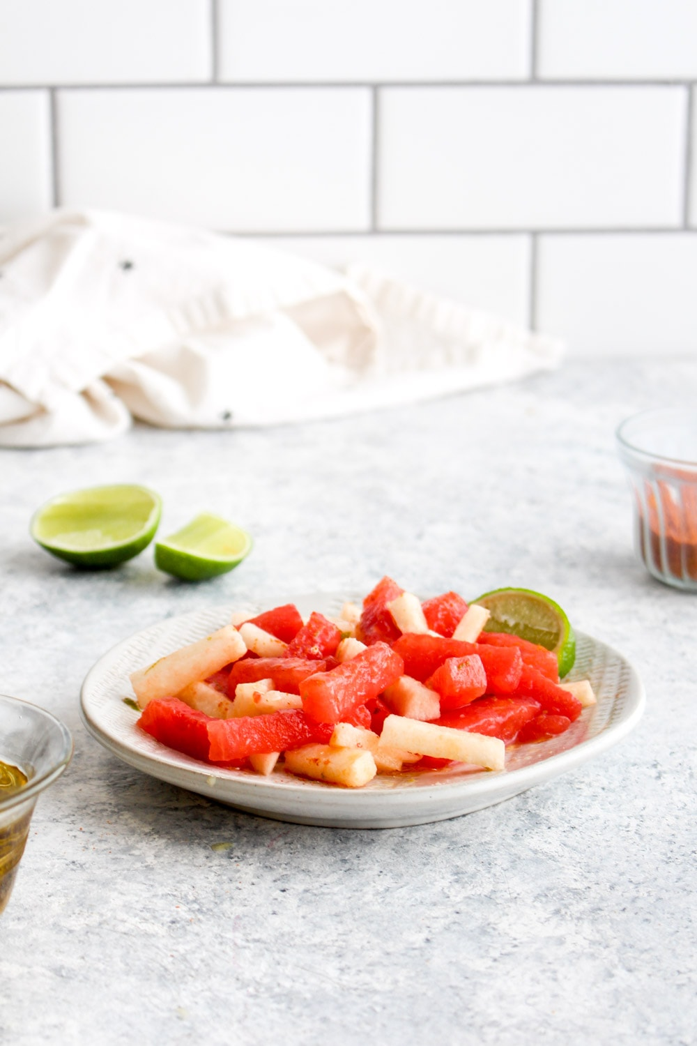 A white plate with watermelon jicama salad and lime.