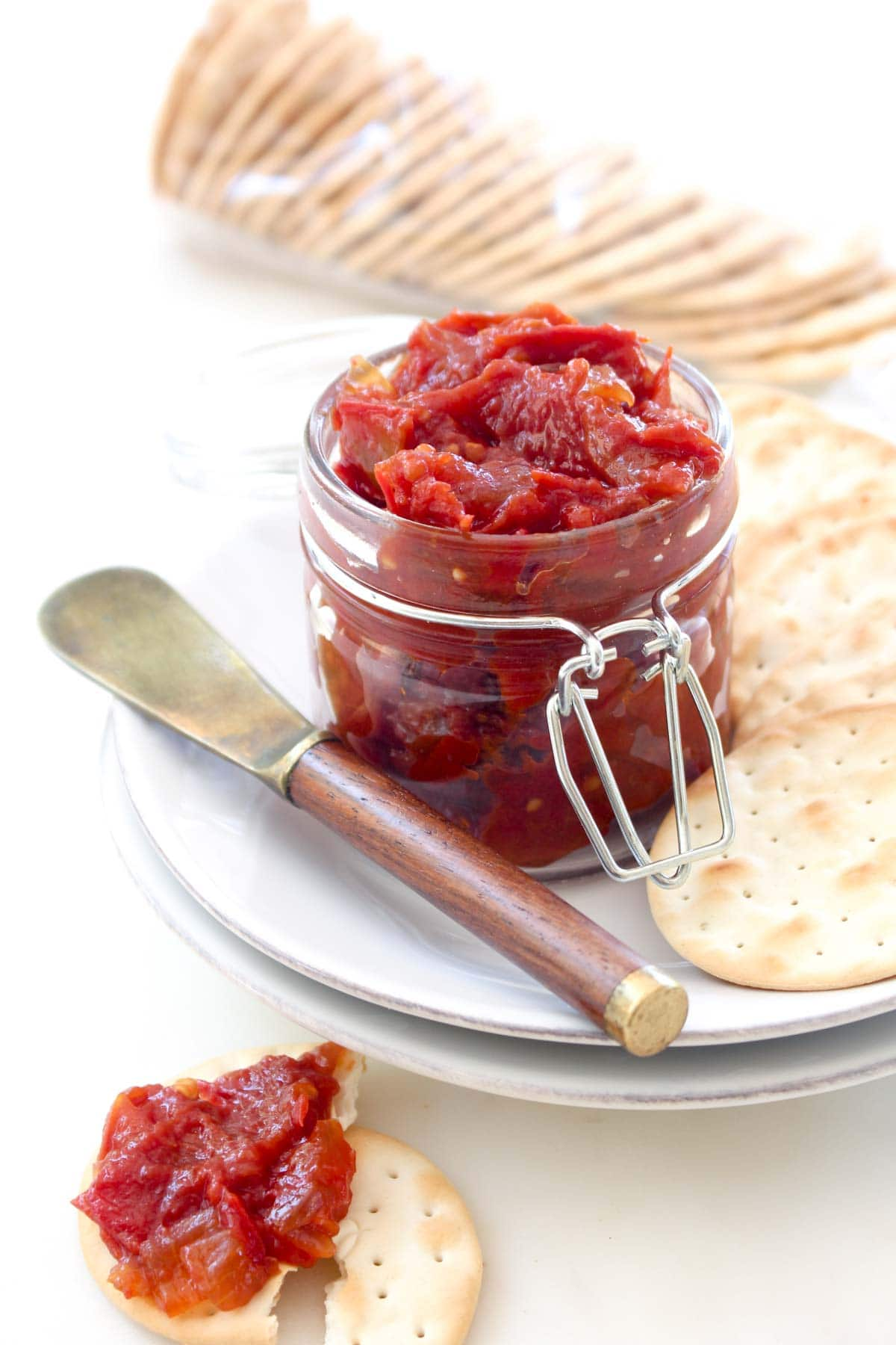 A one pot and one step recipe for homemade tomato jam! The perfect way to use up end of summer tomatoes. This spread is great on sandwiches, crackers, and the perfect addition to your cheese plate.
