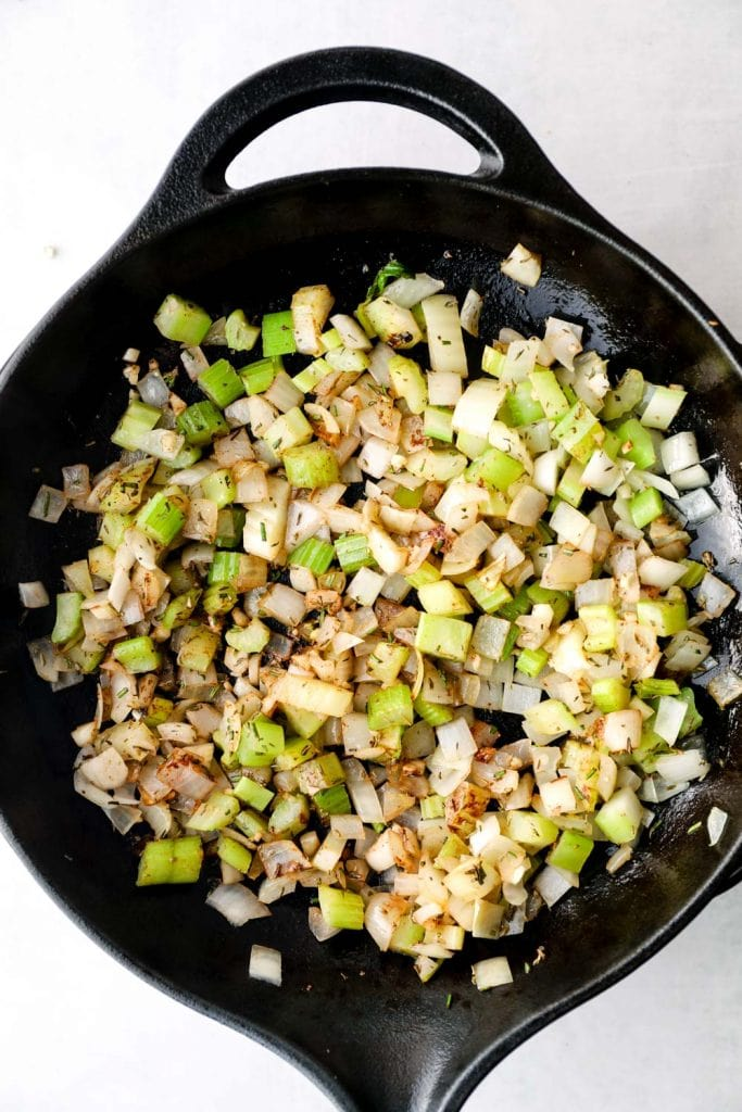 Sautéed onion, celery, garlic, and herbs in a cast iron skillet.