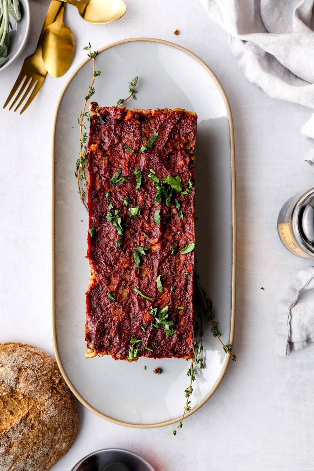 Butternut Squash Lentil Loaf on a serving plate with herbs.