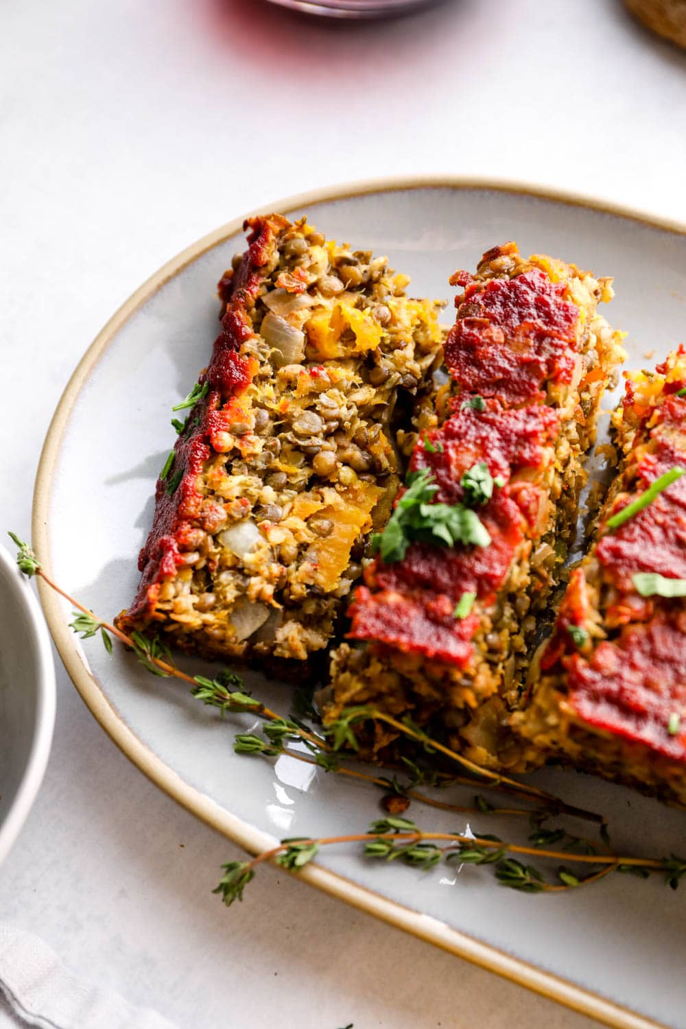 Butternut Squash Lentil Loaf cut into slices and topped with herbs.