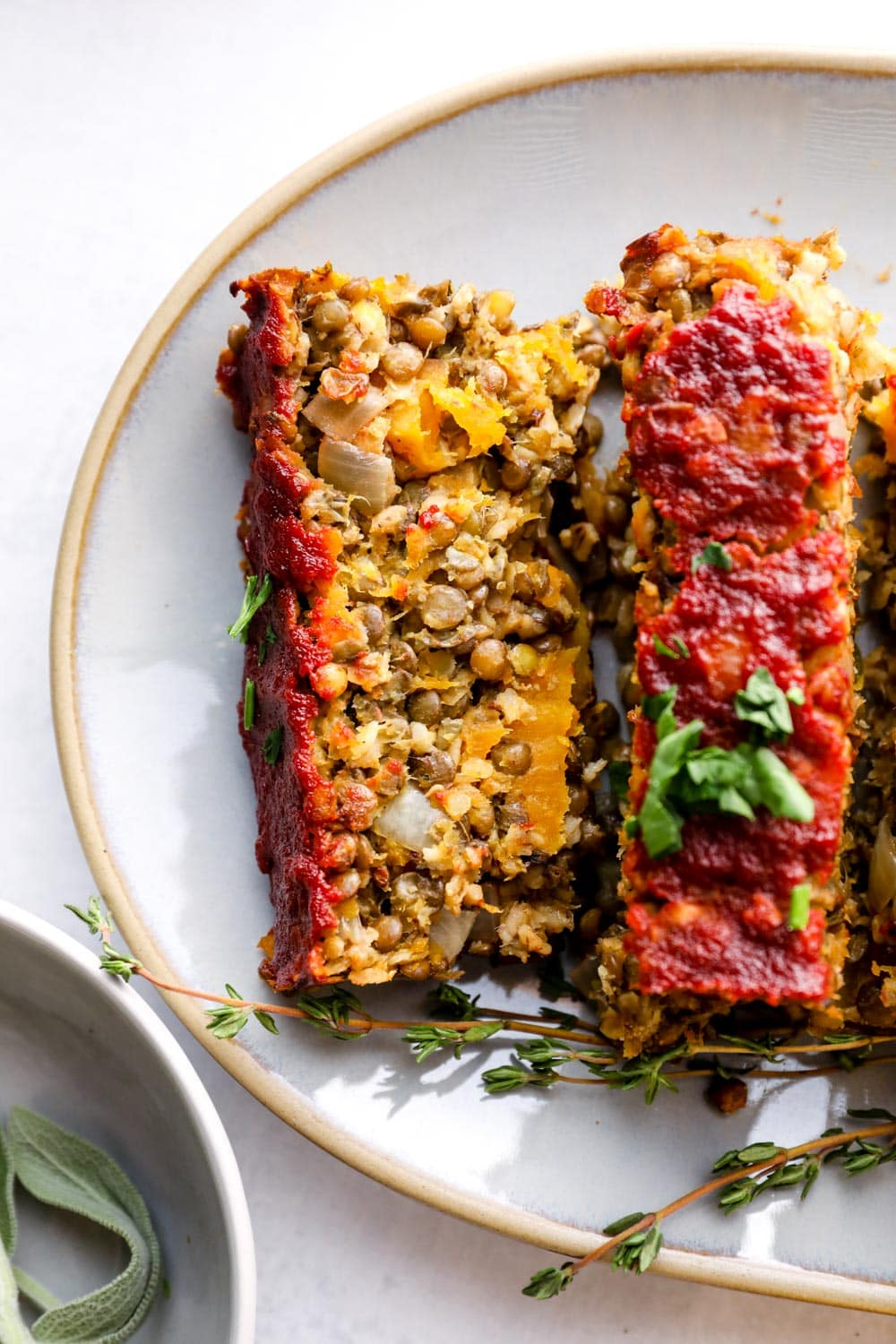 A closeup of a sliced piece of lentil loaf with butternut squash pieces.