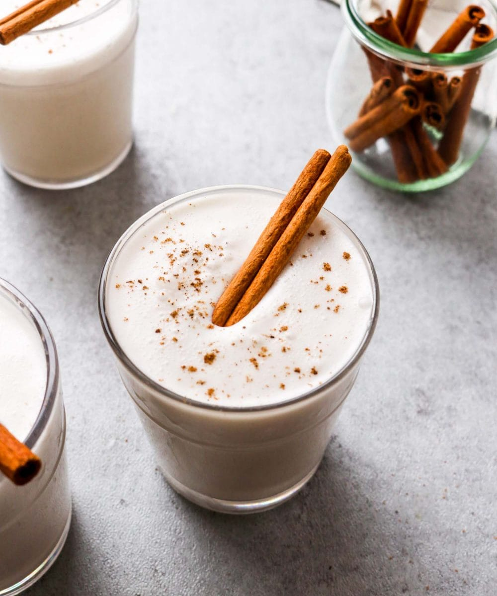 Vegan eggnog in a glass with cinnamon and nutmeg.