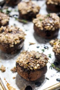 These Vegan Stuffed Mushrooms are a fast and easy party appetizer recipe with less than 10 ingredients! They are filled with nutty walnuts, salty olives, and fresh herbs and finished with a drizzle of sweet balsamic glaze. | CatchingSeeds.com