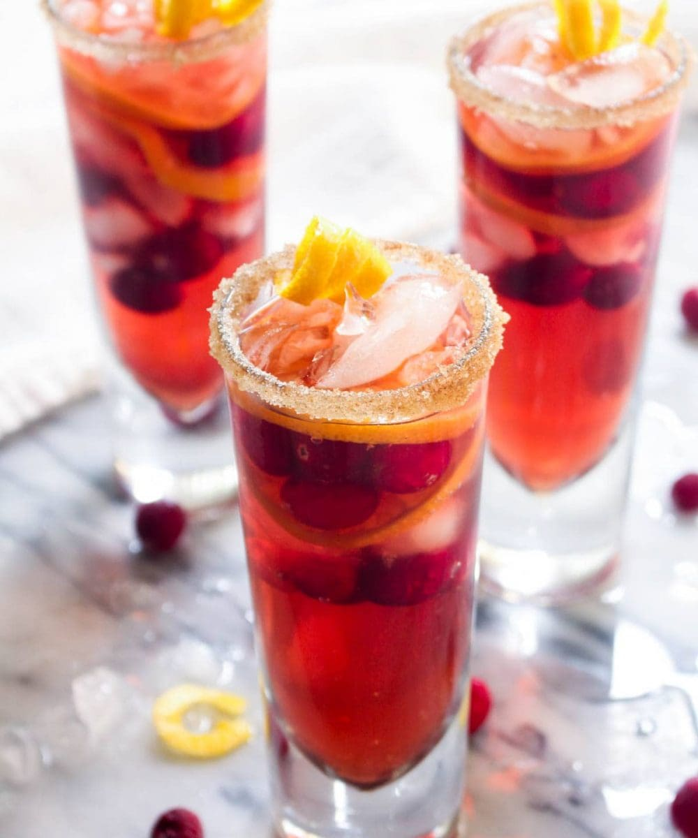 This Kombucha Sangria recipe is a non-alcoholic party drink. Effervescent kombucha gives it a sophisticated feel and cranberries and orange slices infuse this healthy drink with holiday flavor. | CatchingSeeds.com