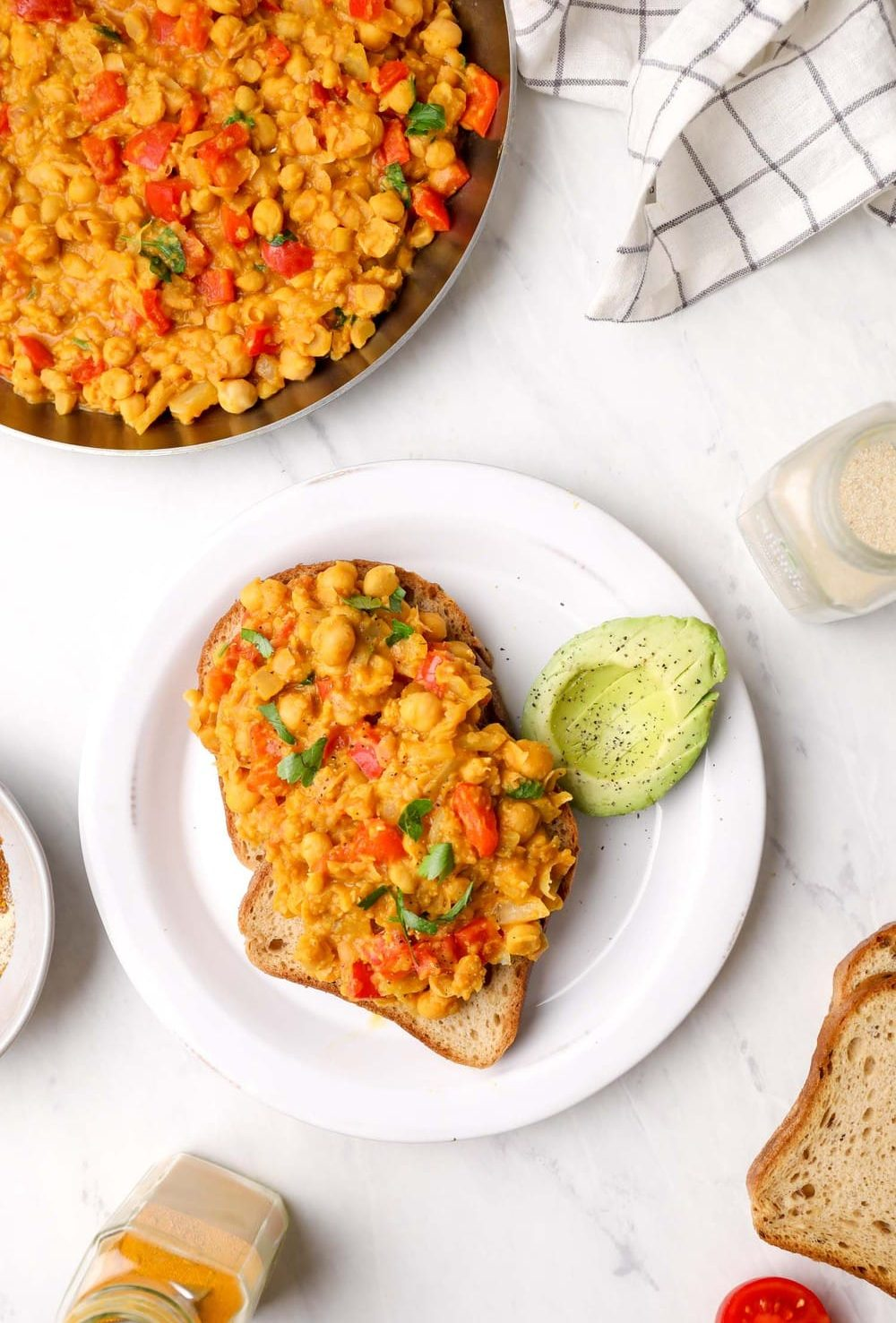 Two pieces of toast with chickpea scramble and avocado.