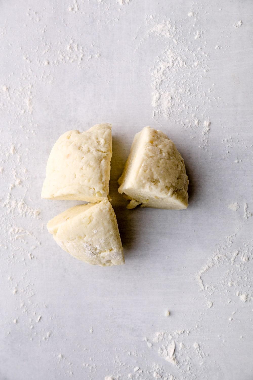 Gluten free gnocchi dough divided into quarters.