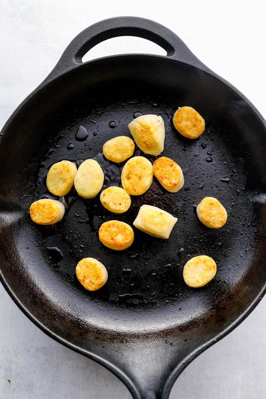 Gluten Free Gnocchi golden brown in a cast iron skillet.