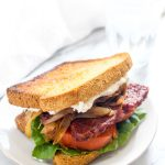 This Smokey Tempeh Sandwich recipe has it all. Sweet and smokey tempeh, zippy horseradish aioli, fresh juicy tomatoes, and sweet and savory caramelized onions. It is like a gluten-free and vegan BLT on steroids! | CatchingSeeds.com