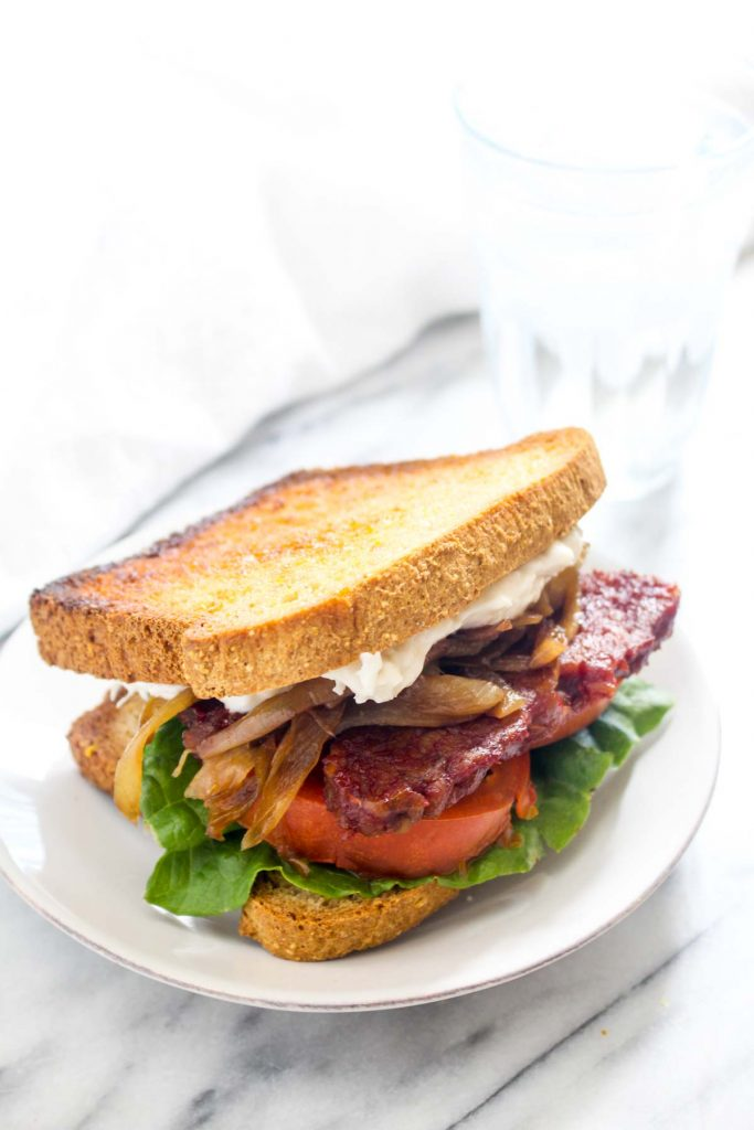 This Smokey Tempeh Sandwich recipe has it all. Sweet and smokey tempeh, zippy horseradish aioli, fresh juicy tomatoes, and sweet and savory caramelized onions. It is like a gluten-free and vegan BLT on steroids!   CatchingSeeds.com