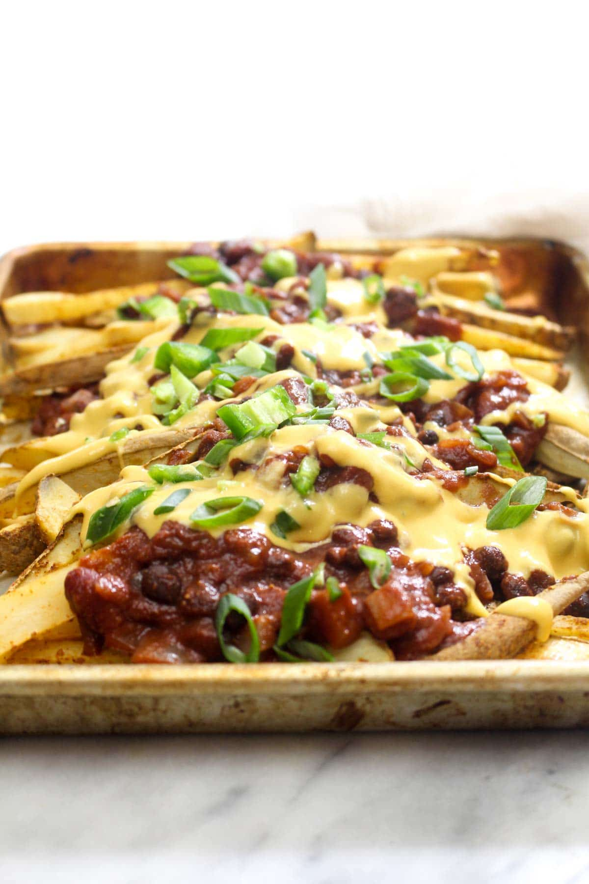 These Vegan Chili Cheese Fries are layers and layers of flavor. They are the perfect recipe for a game-day party, and healthy enough to eat as a weeknight dinner! | CatchingSeeds.com