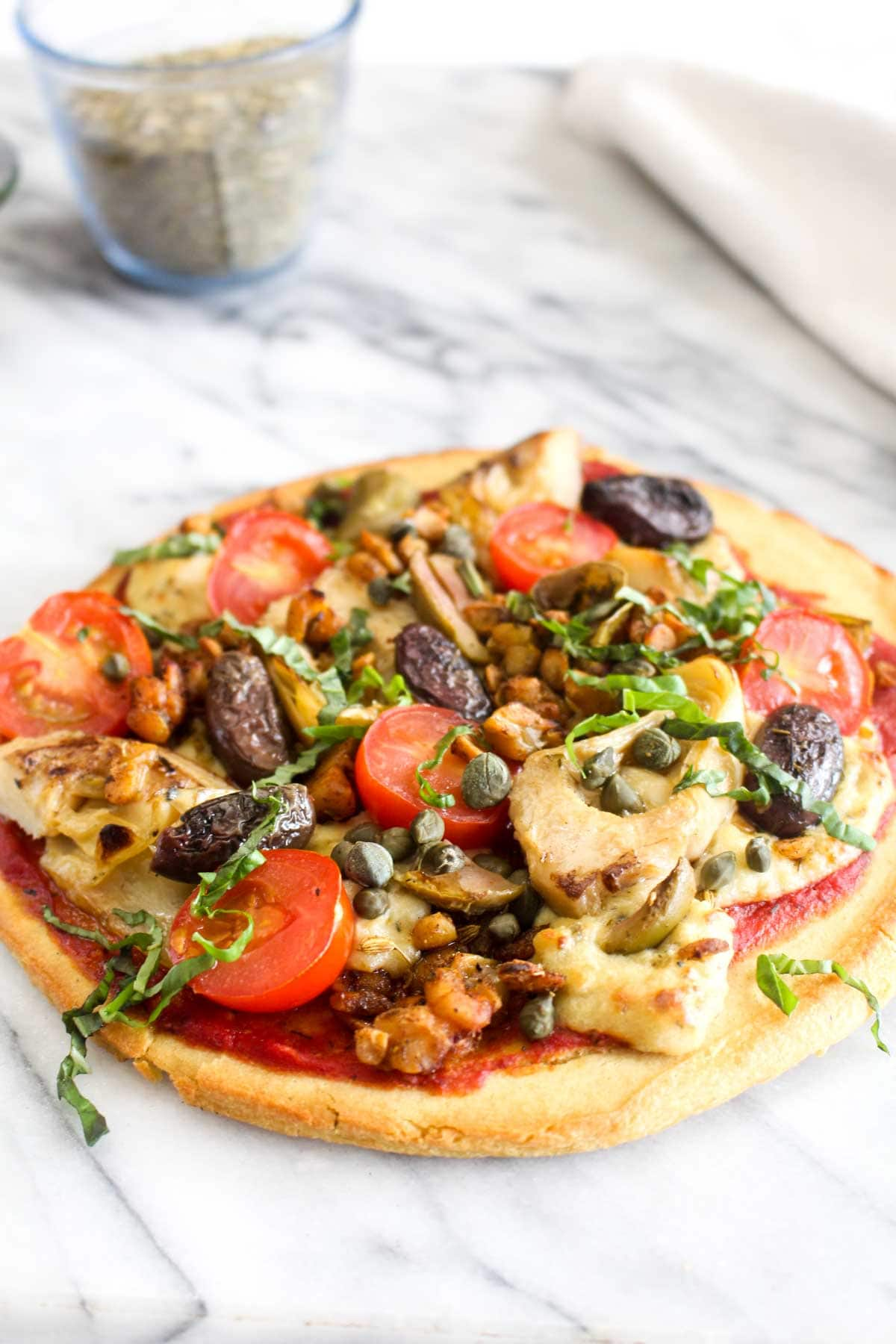 This Vegan Antipasti Pizza with Gluten Free Socca Crust is an allergy-free pizza recipe that everyone will enjoy. It is smothered in melty cheese and a host of flavorful toppings. | CatchingSeeds.com