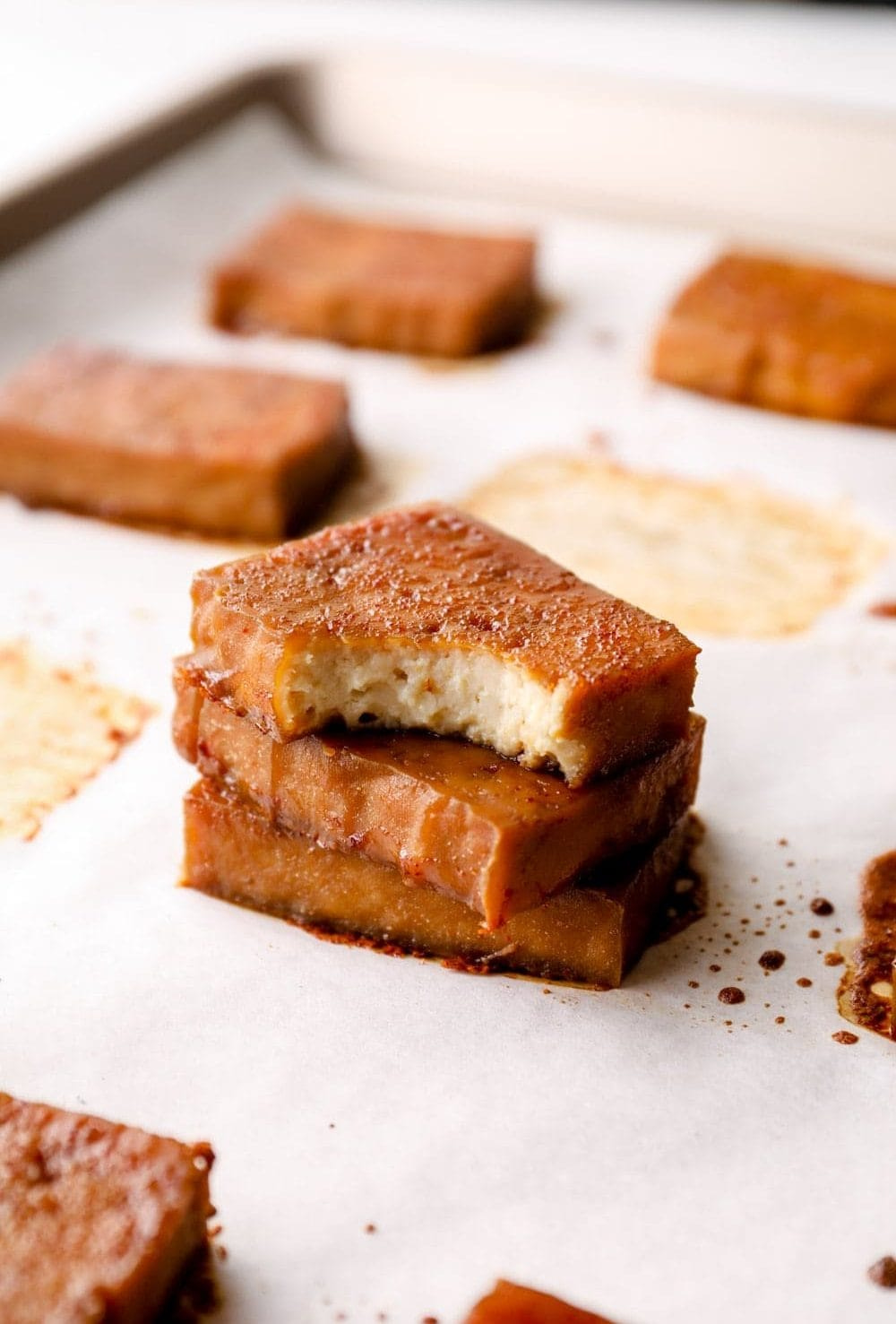 A stack of baked tofu with a bite out of the top piece.