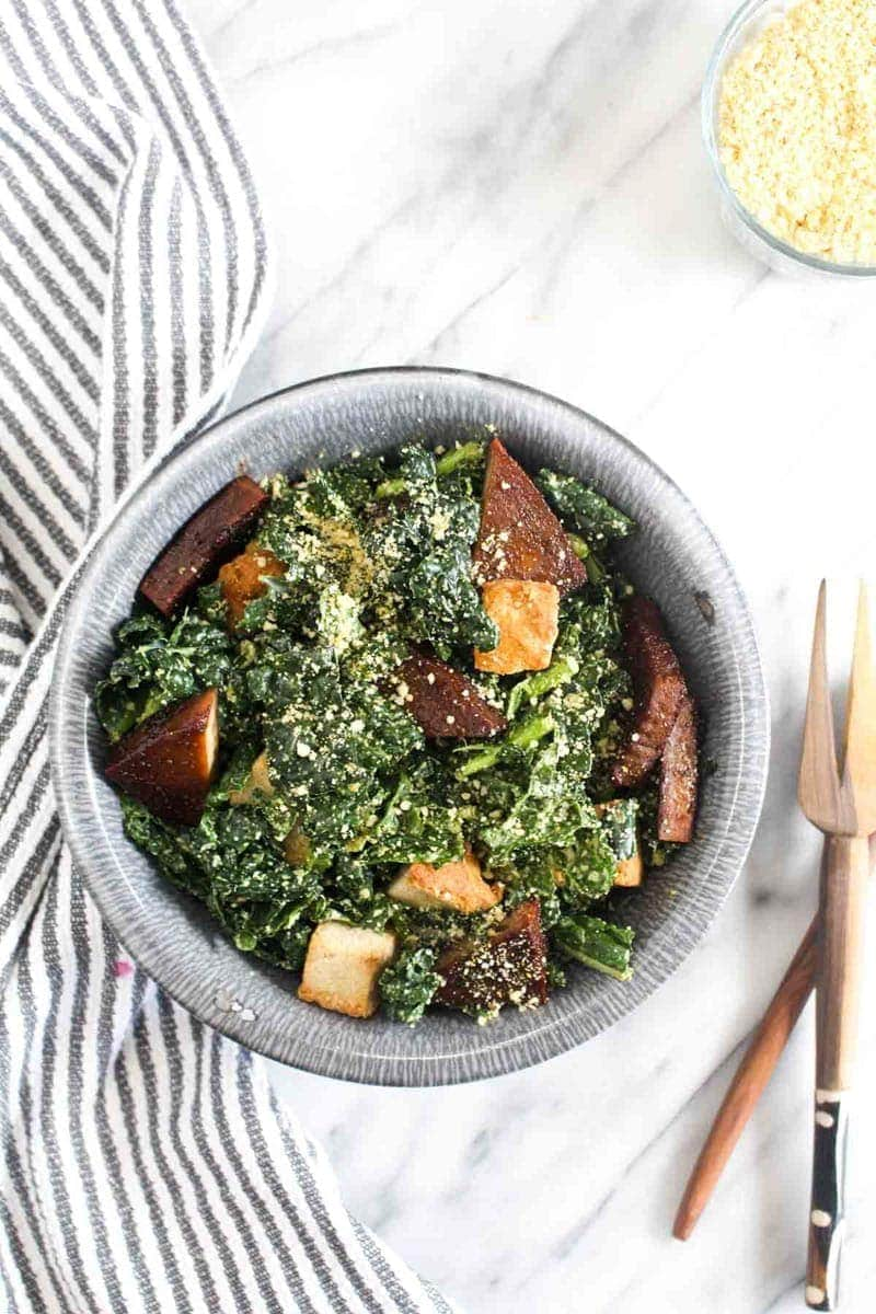 Kale Caesar Salad in a bowl with salad tongs garnished with vegan parmesan cheese, croutons, and baked tofu with a striped towel.