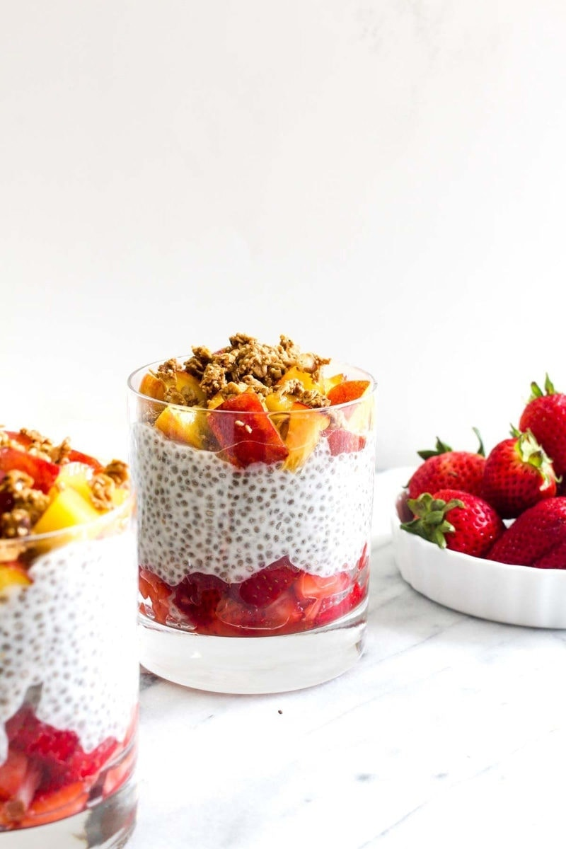 A cup filled with sliced strawberries then chia seed pudding then chopped peaches with granola with a side bowl of strawberries.