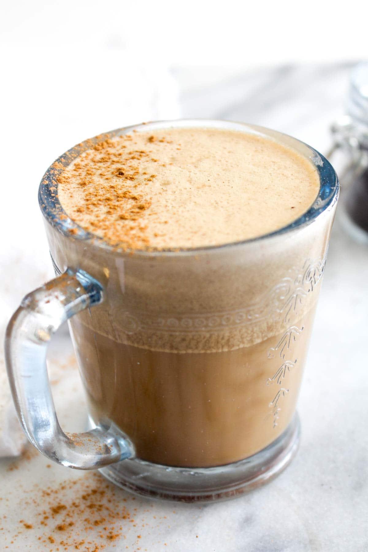Side view of vegan oil free bulletproof coffee with foam and cinnamon.
