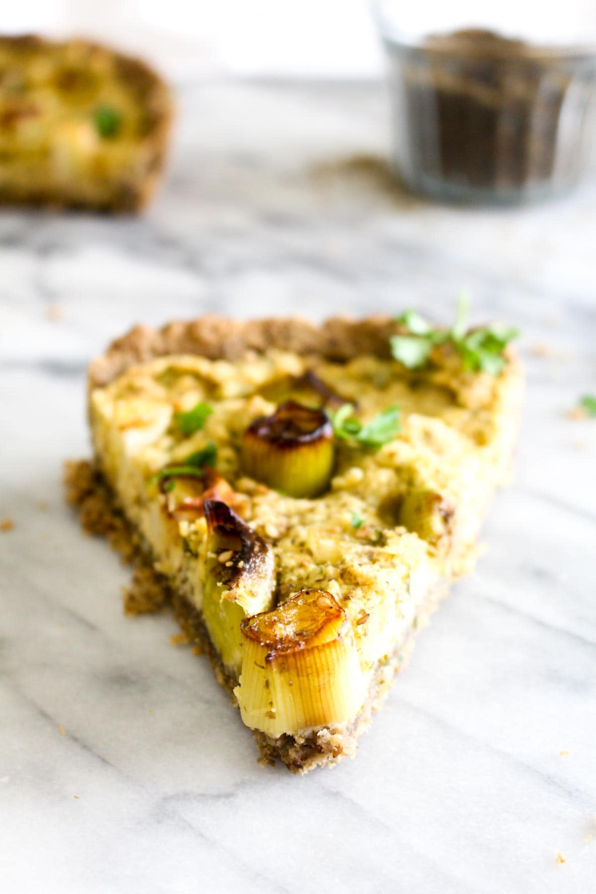 A slice of tart filled with hummus and leeks topped with za'atar and parsley.