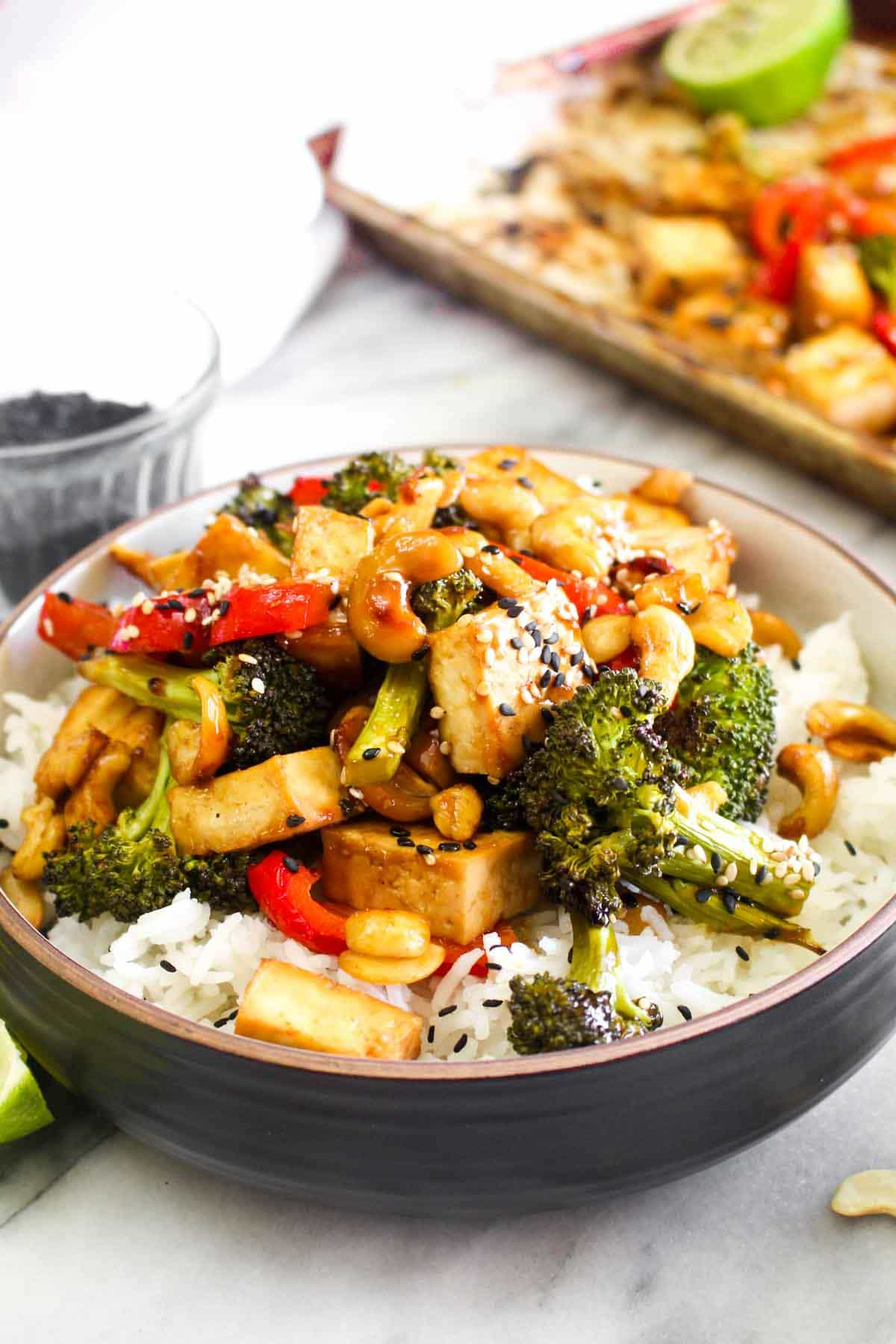 Chinese Cashew tofu in a bowl over rice with bell pepper, broccoli, cashews, sesame, and lime.