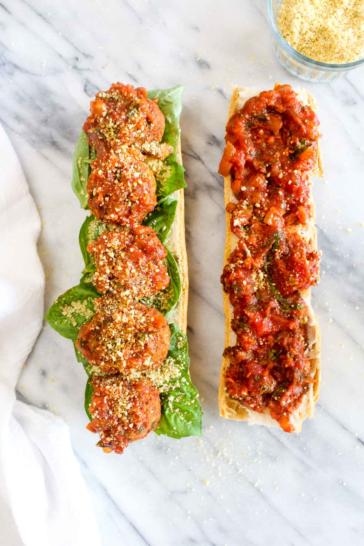 A white baguette with one side covered with basil, vegan meatballs, and parmesan, and the other side covered with marinara sauce on a marble background.