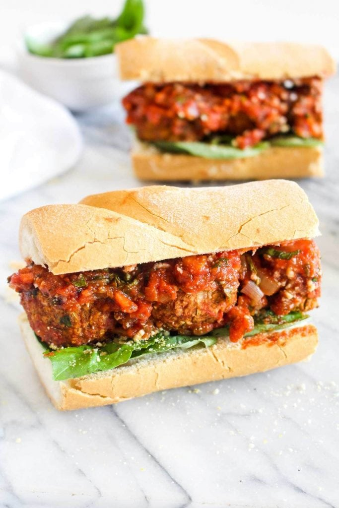 Two vegan meatball sandwiches with marinara sauce and basil on a white roll.