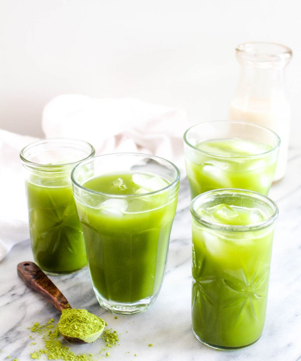 Four glasses of iced coconut water matcha with a spoonful of matcha tea on the side.