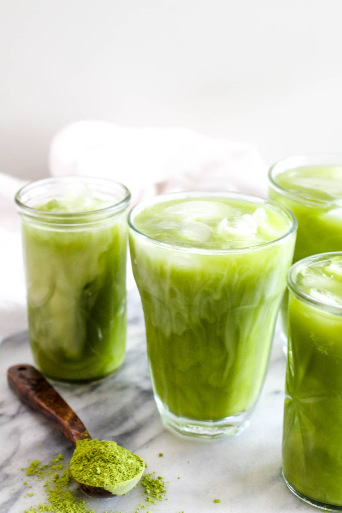 A glass of iced coconut water matcha with a splash of coconut milk.