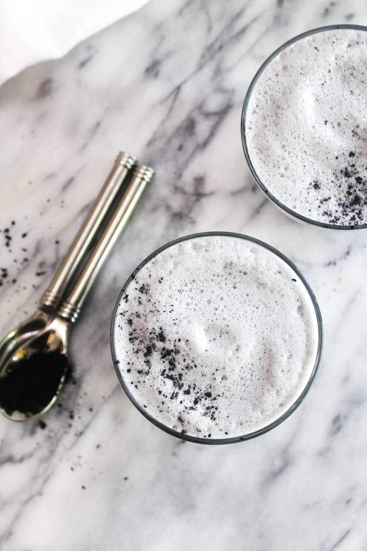 A top view of two black charcoal latte with foam and charcoal sprinkled on top.