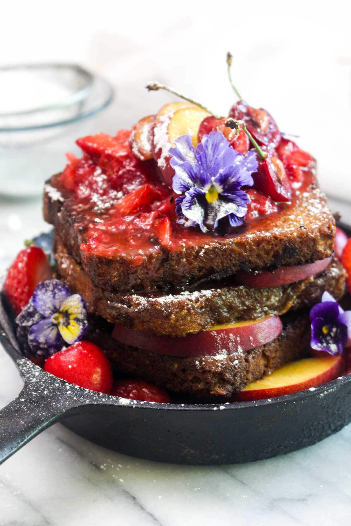 A closeup of a cast iron skillet with a stack of french toast with strawberry sauce, flowers, powdered sugar, and peaches.