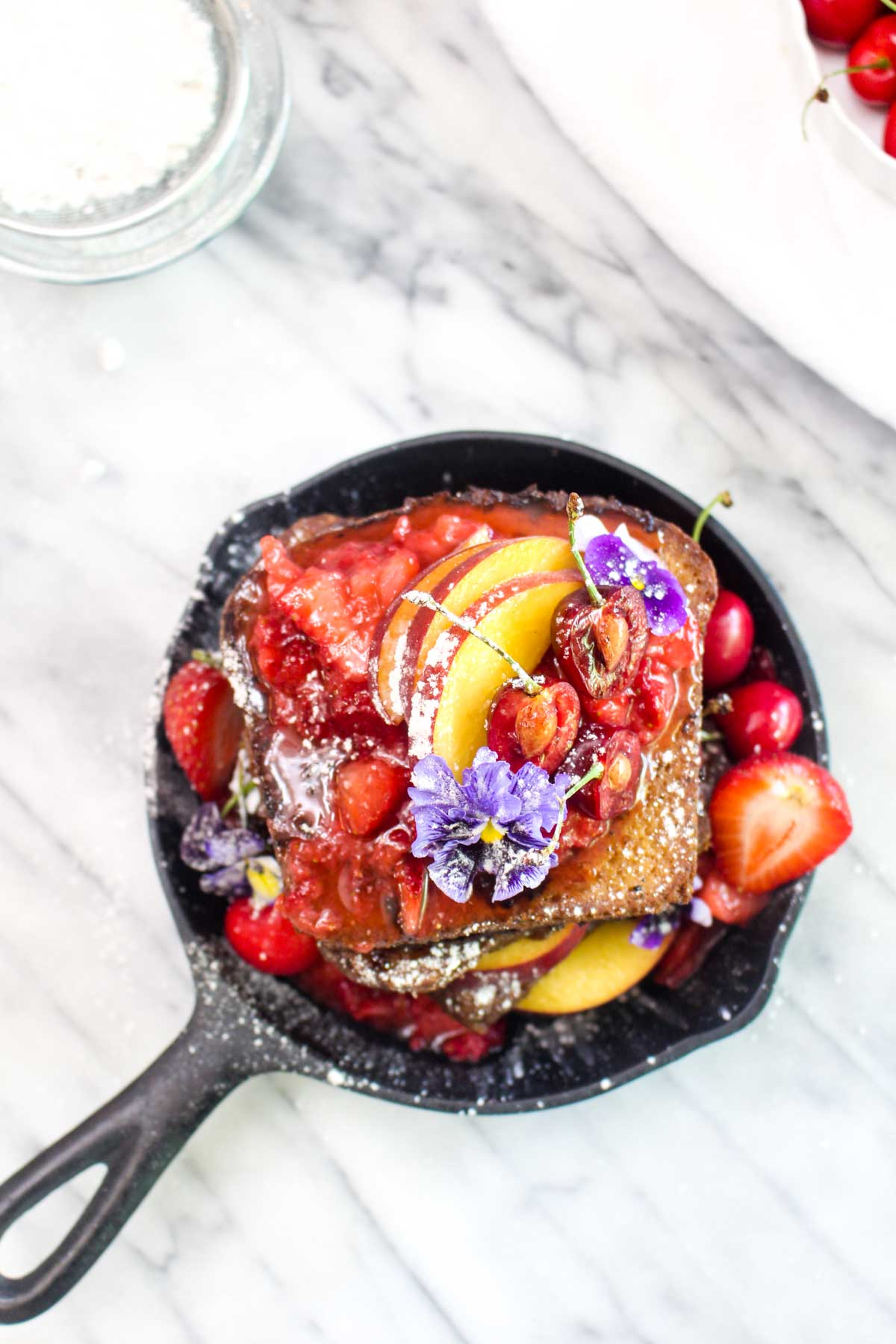 A top view of a cast iron skillet with a stack of french toast with strawberry sauce, flowers, powdered sugar, and peaches.