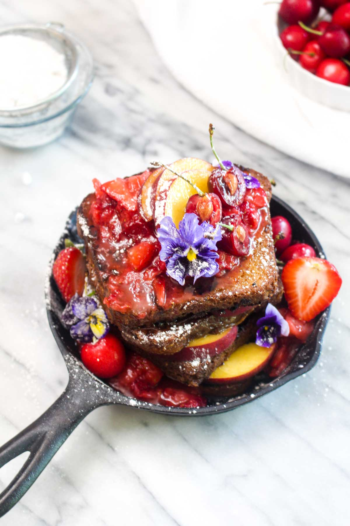 Three quarters view of a cast iron skillet with a stack of french toast with strawberry sauce, flowers, powdered sugar, and peaches.