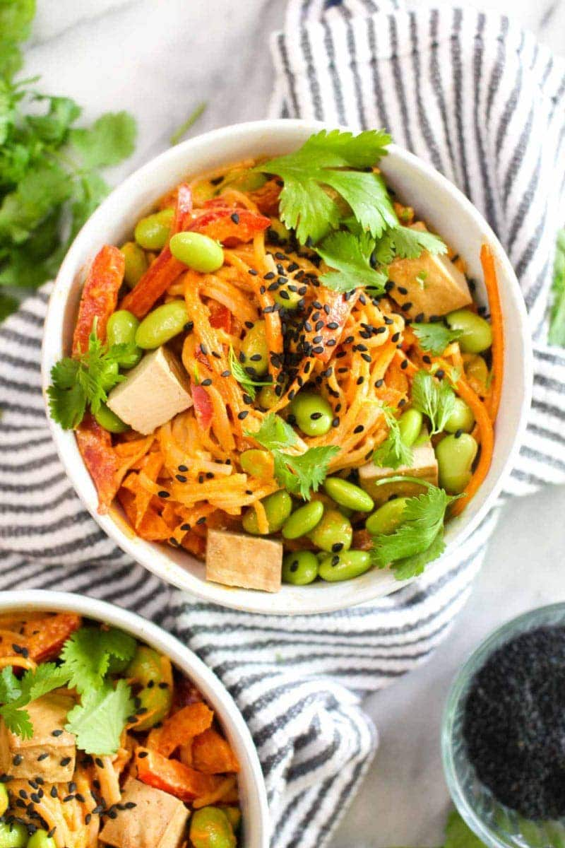 A bowl of noodles with veggies in a Thai red curry sauce with cilantro and sesame.