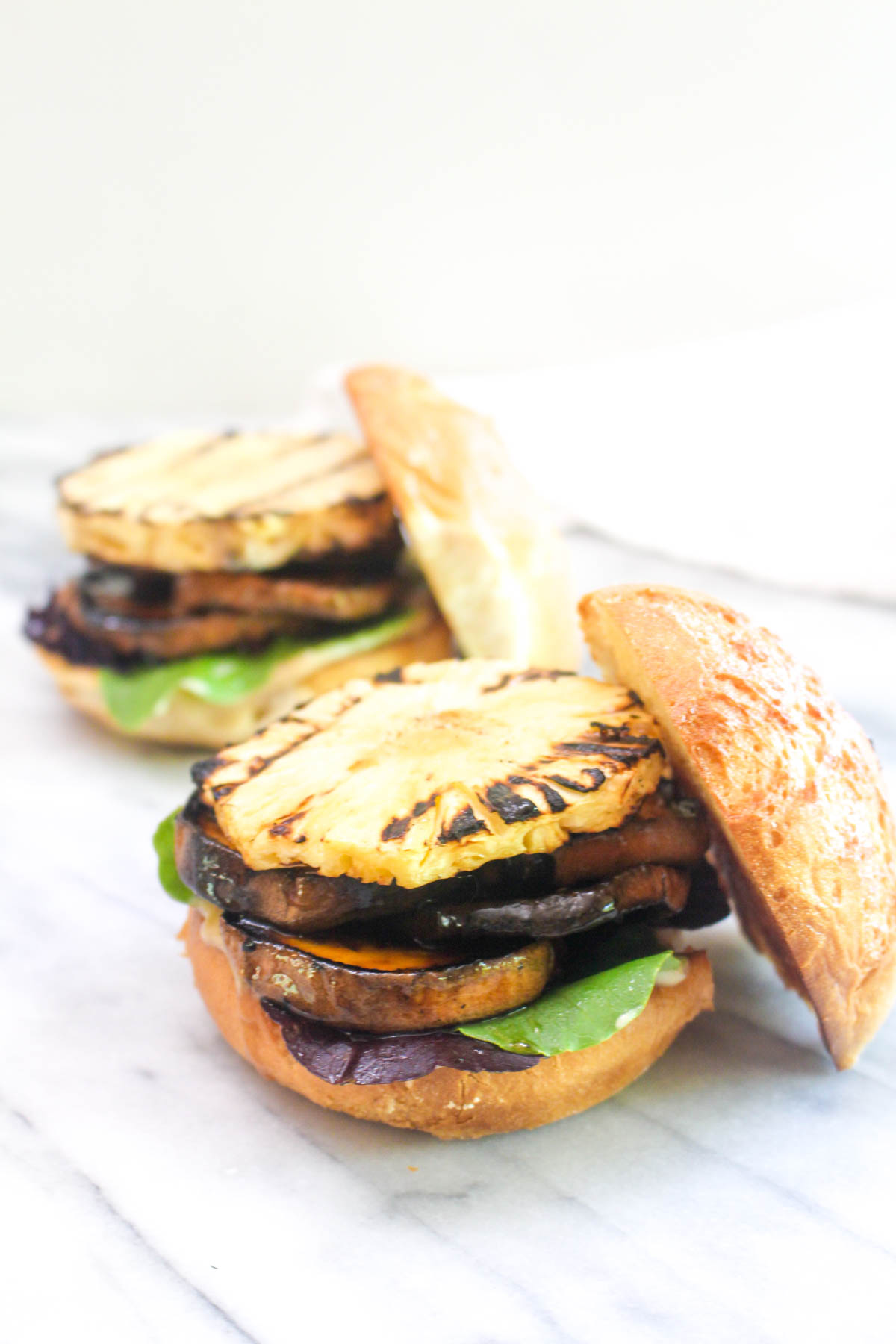 Two burger buns filled with grilled sweet potatoes, grilled pineapple, and mixed greens with the top buns off.