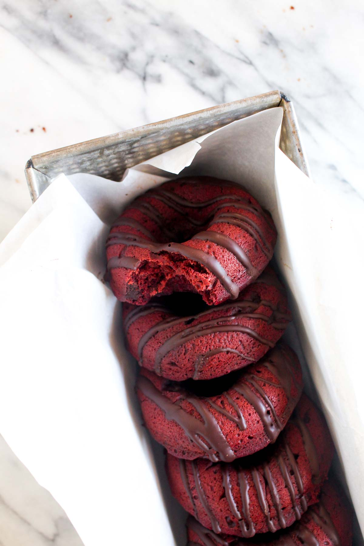 These Baked Double Chocolate Beet Donuts might sound strange, but they are deeply chocolaty, rich and have the perfect soft texture. This healthy dessert recipe is vegan and gluten-free. | CatchingSeeds.com