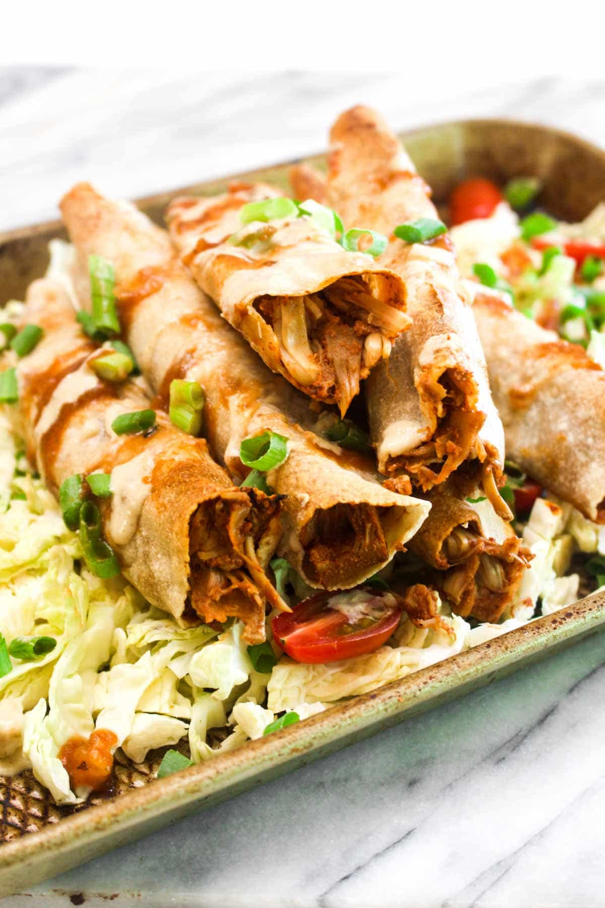 These Jackfruit Taquitos are filled with decadent jackfruit that looks and tastes like vegan pulled pork! This healthy gluten free recipe is baked rather than fried for crispy exteriors without any of the guilt. | CatchingSeeds.com