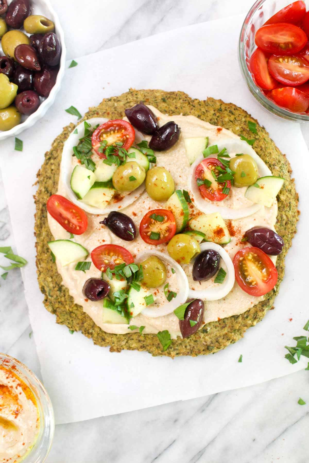 A falafel crust topped with hummus, olives, onion, tomatoes, and parsley.