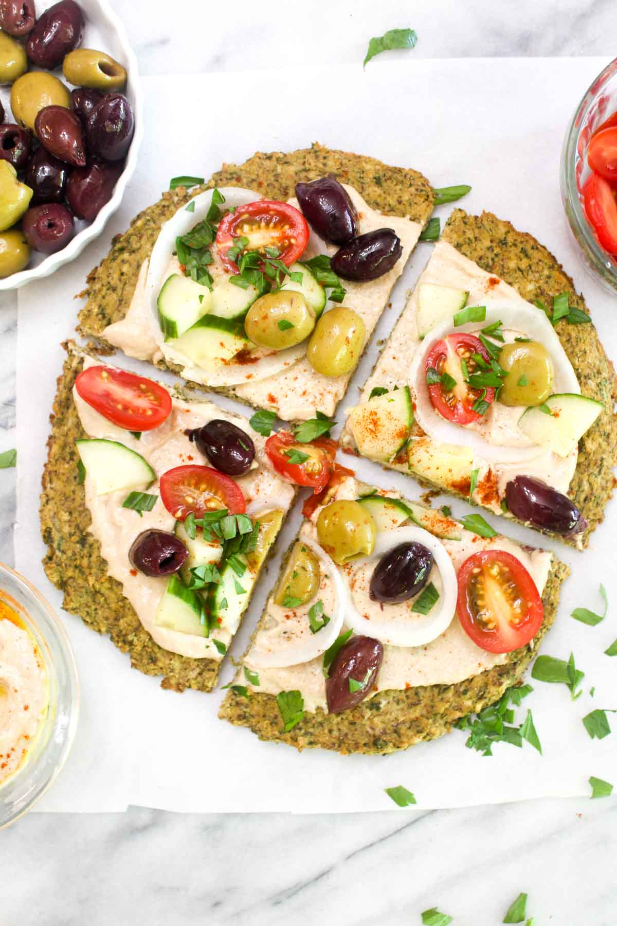 A falafel crust topped with hummus, olives, onion, tomatoes, and parsley cut into four slices.