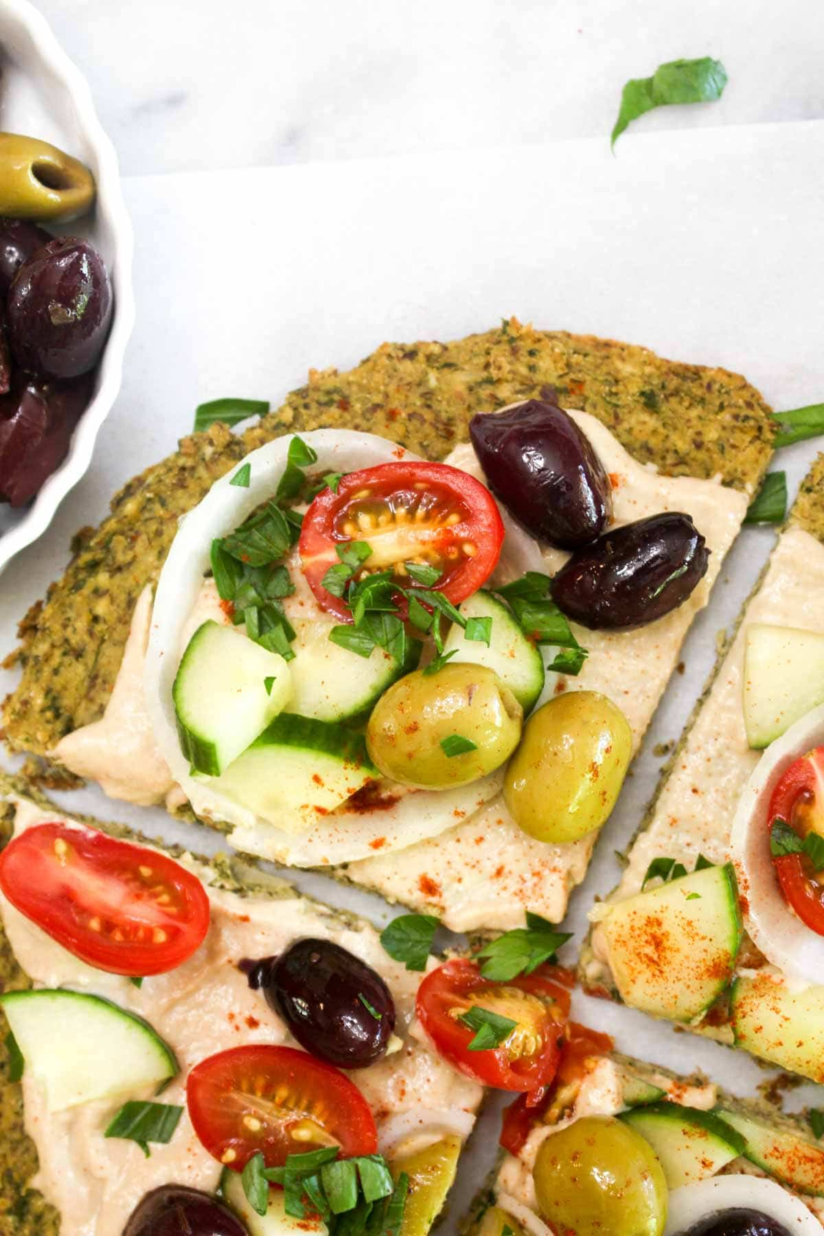 A a closeup of a slice of falafel crust topped with hummus, olives, onion, tomatoes, and parsley.