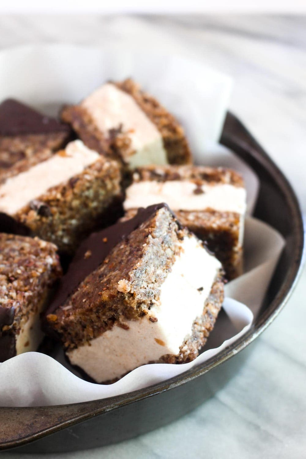 These Healthy Ice Cream Sandwiches are raw, paleo, vegan and gluten free! Smooth vanilla ice cream gets sandwiched between two chocolate cookies for a decadent and healthy dessert which only requires 20 minutes of hands on time! | CatchingSeeds.com