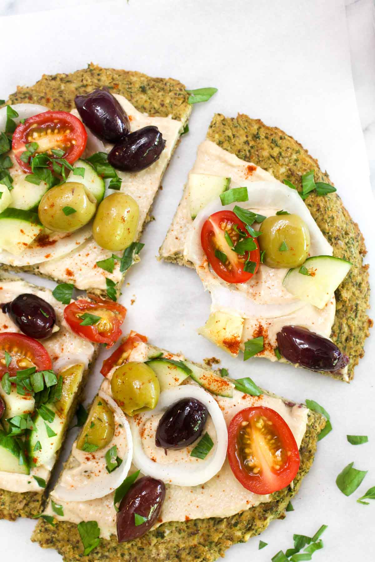 A a closeup of a slice of falafel crust topped with hummus, olives, onion, tomatoes, and parsley with a bite out of it.